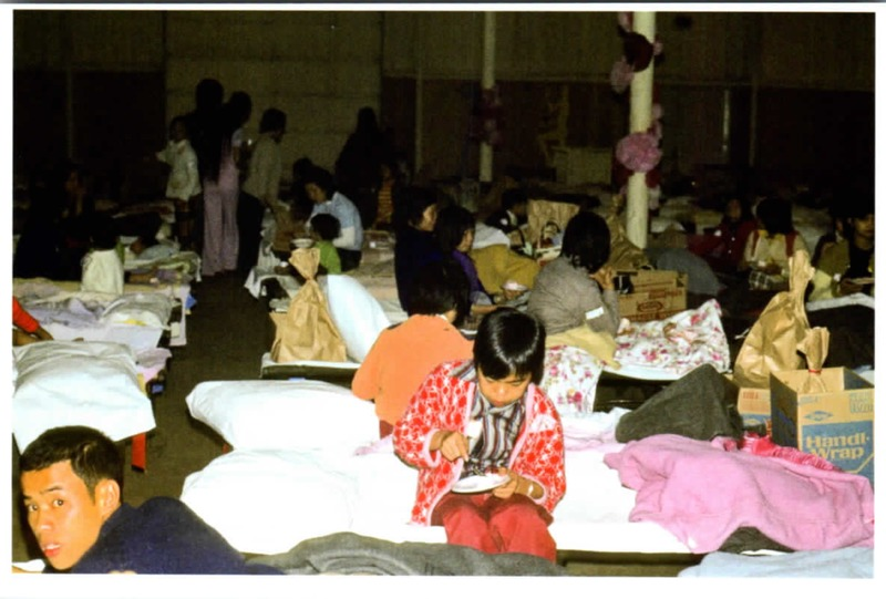 Vietnamese immigrants sitting on cots with child eating<br />