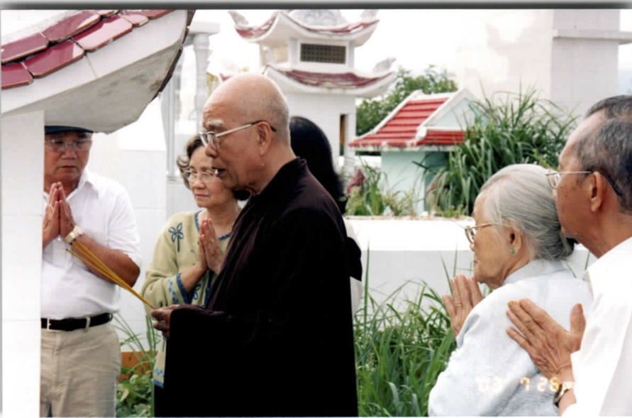 Photo of family in prayer with monk